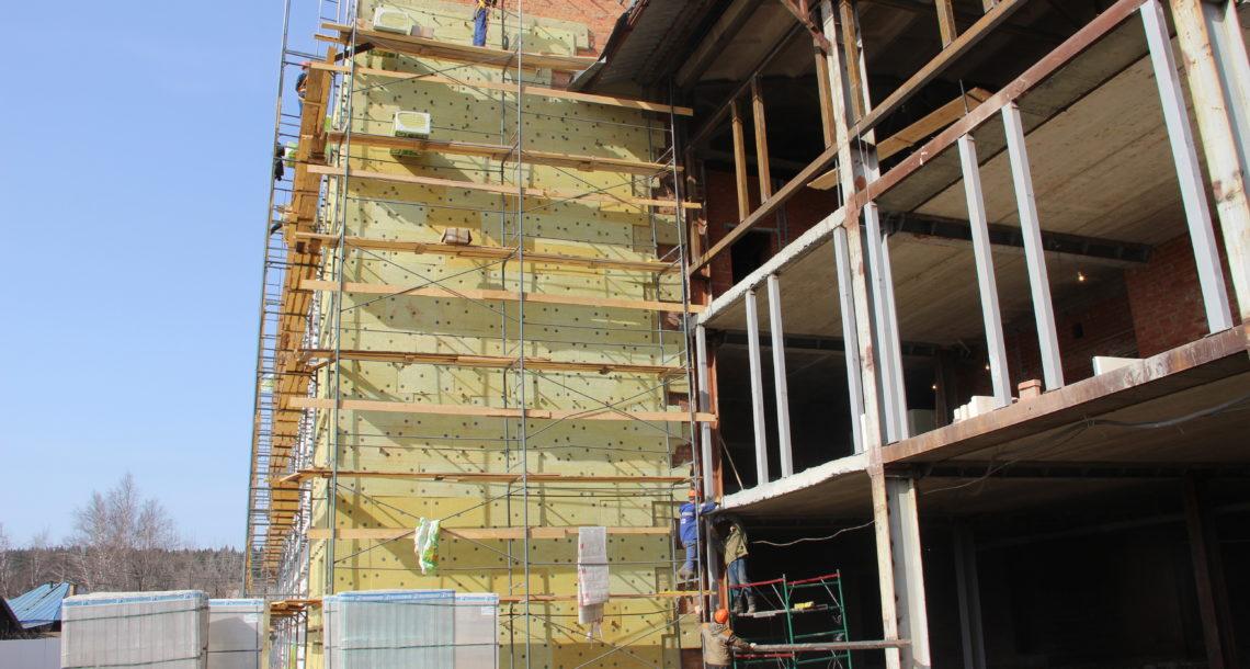 Строители утепляют готовую часть фасада